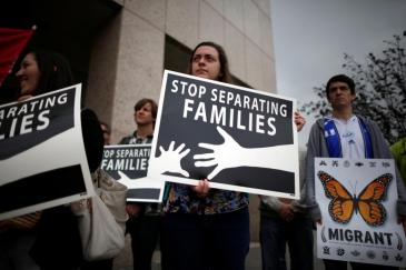 People hold signs at a protest against plans to deport Central American asylum seekers in Los Angeles